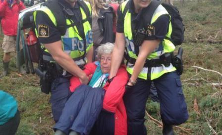 Polisen bär bort en äldre dam